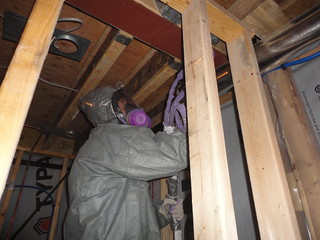 Spray foam technician seals cracks in basement...