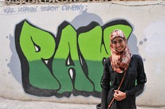 Cast member Layan Rakka in front of PAW, Inc. street art in Dahiye, Lebanon.