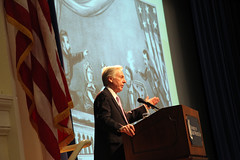 Stewart lectures in front of drawing of Lincoln assassination
