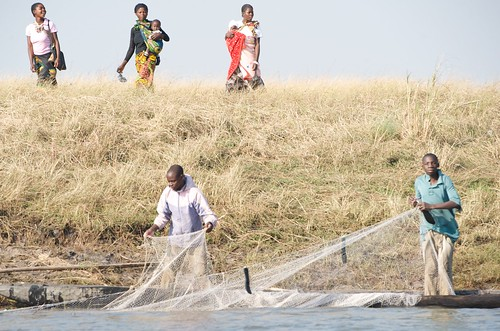 Women head to market, as men pull in nets, Zambia. Photo by Patrick Dugan, 2012.
