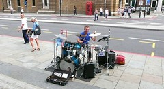 Solo street sound stunt. (davidezartz) Tags: street leica uk greatbritain blue windows light red summer england people musician brown white signs black green london sunshine yellow grey shadows drumset pavement great solo sound drummer busker streetmusic sounds telephonebox stunt greatmusic onemanband thoroughfare thegalaxy leicadlux3 thesoundsofsummer vigilantphotographersunite vpu2 vpu3 vpu4 vpu5 vpu6 vpu7 vpu8 vpu9 vpu10 frameitlevel1 frameitlevel3 frameitlevel2 frameitlevel4 solostreetsoundstunt