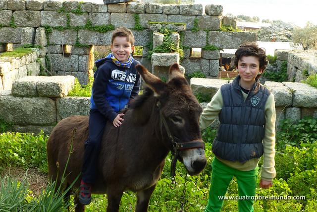 Unai montado en un burro del pueblo mientras Ada lo sujeta