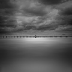 BROODING SKY! (Nick green2012) Tags: uk longexposure bw white seascape reflection wet water overgrown monochrome clouds dark square landscape chains seaside still alone shine shoreline highlights silouette calm minimal coastal filter squareformat ten beaches seafront sunrays minimalist hightide seapool 10stop iplymouth