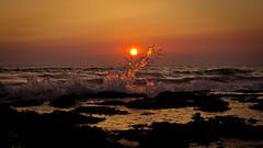 Ola rompiendo en puesta de Sol