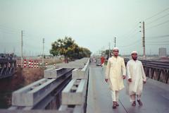 An Evening Walk with Muslims... (Sheikh Shahriar Ahmed) Tags: life street bridge film analog 50mm evening nikon steel candid muslim islam young fujifilm dhaka nikkor f18 bangladesh punjabi nikonf6 tupi af50mmf18d fujicolorc200 dhakadivision aftabnagar epsonv330 huzurs sheikhshahriarahmed