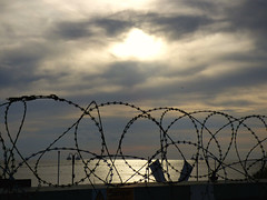 Behind the wire (Peanut1371) Tags: razorwire wire sun sea clouds cleethorpes