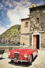 Lancia roadster at Vernazza, Italy (Randy Durrum) Tags: red italy church clouds canon eos harbor europe eu samsung convertible m cinque lancia roadster durrum leuropepittoresque snapseed