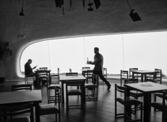 Coffee break (Georgie Pauwels) Tags: museum lanzarote blackandwhite public streetphotography moment waiter tables chairs window olympus