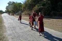 The Dismount - Mrauk U, Rakhine, Myanmar Burma (John Meckley) Tags: red water kids vanishingpoint robe burma buddhist perspective buddhism monks myanmar burmese rakhine shoulderpole