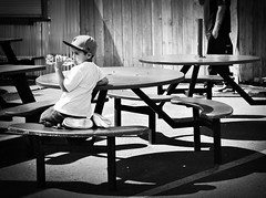 Water Boy (iamamylou) Tags: boy child tables bw hat baseballcap benches shadow waterbottle drinking water black white