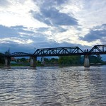 The infamous Bridge over the River Kwae at dusk seen from a long-tail boat, Kanchanaburi, Thailand thumbnail