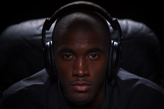 Moody Portrait of Man Listening to Music (Hal Bergman Photography) Tags: portrait people music man black color horizontal dark person intense focus sitting moody serious dramatic listening photograph portraiture stare headphones africanamerican studioshot focused 30s oneperson intensity 20s seriouslook oneman onepersononly shallowfocus lookingatcamera onemanonly focusonforeground africandescent neutrallook