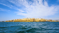 View from the sea to the ancient Akko against a beautiful sky. (mamanata) Tags: history fort acco sky architecture sea medieval stone wall famous israel blue east water ancient city travel tourism old feature building fortified coastline nature structure mediterranean israeli harbor built past countries tourist outdoors cityscape exterior sunlight sun landscape locations strength nautical national colors backgrounds bay geographical summer cloud crusades edge panoramic stronghold archaeology wave protection