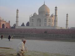 Indian man on his haunches near the Taj Mahal India.