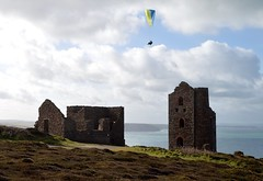 New technology flies over the old. (rustyruth1959) Tags: nikon nikond3200 tamron16300mm uk cornwall kernow porthtowan st agnes whealcoatestinmine tinmine mine tin buildings enginehouse structure stone ruins disused outdoor hangglider sea atlantic water ocean person clouds sky cliffs windows grass coast shoreline canopy mining tinmining walls green