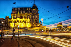Victoria Hotel and passing tram (PaulHoo) Tags: amsterdam night city urban longshutterspeed evening blue hour 30sec traffic light lightray holland netherlands 2017 victoria hotel tram speed