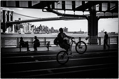 one wheel up ... nyc (michael baumann) Tags: newyork bicycle brooklyn river bench chat downtown waterfront manhattan walker brooklynbridge eastriver biker onewheel 2013 michaelbaumann eastriverbikeway