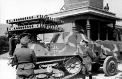 "German high officer ( probably Rommel) inspecting a Panzerwerfer auf Halbkettenfahrzeug ""Maultier"" ( half-track with multiple rocket launcher). North France, Riva-Bella 30 May 1944"