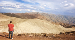 Storm heading in from the South... (Trapac) Tags: california travel autumn red panorama usa man mountains male tourism standing person high nikon looking view south watching dreaming jeans figure photomerge deathvalley geology lookingdown nikkor overlooking viewpoint gazing teeshirt contemplating blackmountains furnacecreek deathvalleynationalpark dantesview wmh nikkor3570mm amargosarange d700 nikond700 coffinpeak owlsheadmountains tracypackerphotography wwwtracypackercom viewpointterrace 1669metres 5476feet mesozoicvolcanos flickrmarketplace