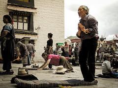 Prostrate oneself on the ground  (dotstone) Tags: china old man nikon prayer tibet coolpix tibetan lhasa cushion jokhangtemple p7700 joinonespalms
