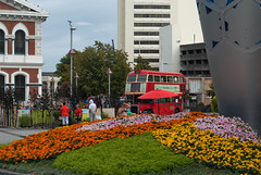 Lots of Bright Colours (Jocey K) Tags: road street flowers newzealand christchurch sky people sculpture sign architecture clouds buildings chalice londonbus festivalofflowers cathedralsq