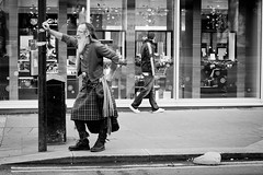 A Clothing Contrast (Leanne Boulton) Tags: life road street city portrait people urban bw white man black men window monochrome face fashion shop contrast standing canon hair walking beard mono scotland blackwhite store clothing kilt post pavement glasgow candid traditional style scene sidewalk human celtic tradition clan leaning facial tracksuit sportswear blinkagain