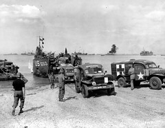 LCT-550 landing Dodge WC54 field ambulances at Normandy, France, June 1944; note snorkel tube for fording streams on lead ambulance.
