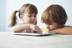 Small kids using a tablet (Nasos Zovoilis) Tags: life city blue boy portrait brown white playing reflection cute love home apple girl beautiful face childhood closeup fun toy happy kid bed eyes hands toddler europe alone child play hand looking little sweet head expression background room small joy young adorable handsome son athens read greece jeans sofa blond attractive casual worry inside charming care tablet hold ipad