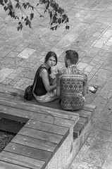 Somebody's Watching Us.jpg (Pauls-Pictures) Tags: street city two people urban black eye boyfriend netherlands photography girlfriend couple sitting photos body eating candid pair watching lovers contact language photograhy almere