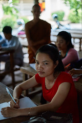 Schoolgirl attending Buddhist Monk teaching, Battambang, Cambodia (Alex_Saurel) Tags: school orientation face pleinformat fullframe portraiture portray halfbody body femme scans moine woman female working monk portrait silhouette adult student work bouddhisme buddhist adolescence position buddhism people girl fille asia type travel lifescene religion imagetype reportage photospecs photoreport photoreportage archicategory qualite main photojournalism stockcategories hand day plantaille cambodge time vertical scènedevie sony50mmf14sal50f14