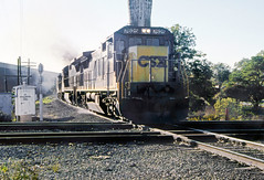 CSX southbound manifest freight train, led by GE C40-8 locomotive # 7625, along with two otherlocomotives, is seen while crossing the Norfolk Southern double diamonds in the commercial business area of Cordele, Georgia, 1990 - 4 (alcomike43) Tags: old city color classic vintage ties town photo downtown crossing ns tracks slide trains historic diamond photograph engines rails ge spikes locomotives railroads ballast generalelectric rightofway csx norfolksouthern mainline roadbed 7625 dieselengines diesels diesellocomotives c408 cordelegeorgia whistlepost southerncrossing dieselelectriclocomotives tieplates signalcontrolbox anglebars conventionaljointedsectionrail diamondprotectionblocksignal weldedribbonrail manifestfreighttrains mixedmerchandisefreighttrains commercialbusinessarea