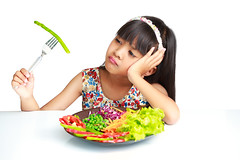 Little asian girl with expression of disgust against broccoli, Isolated over white (Patrick Foto ;)) Tags: portrait people food white cute green girl beautiful face hat childhood female studio asian thailand kid healthy holding child natural little eating expression background young bored lifestyle broccoli vegetable fresh health thai vegetarian concept diet grocery cheerful unhappy isolated nutrition disapproval
