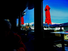 Late lunch with a view of the mountains in Jasper (+1) (peggyhr) Tags: peggyhr spring umbrellas red snow jasper alberta canada dsc08763b travel canadianrockies jaspernationalpark candid thegalaxy thegalaxyhalloffame thegalaxystars infinitexposurel1 thegalaxystarshall0ffame