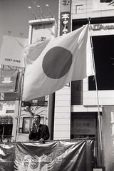 Nationalist, Shinjuku (View Master 187) Tags: leica yellow japan 50mm close near dr delta 11 m summicron filter 100 f2 dual m3 range ilford 20c focusing leitz microphen 10min