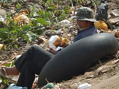 Sitting in a Tube (mikecogh) Tags: hat sitting tube thong rubbish phnompenh riverbank smling