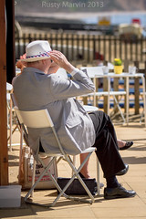 Hopper or Parr - The odd couple (when there was sun) (Rusty Marvin - Imagery by John) Tags: beach hat fence chair couple martin chairs candid edward odd tables sat hopper nottinghill parr