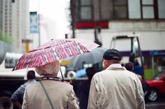 (september.) Tags: nyc newyorkcity pink film rain umbrella 35mm couple midtown canonae1 raining canonfd50mmf14 canonfd fujifilmsuperia400