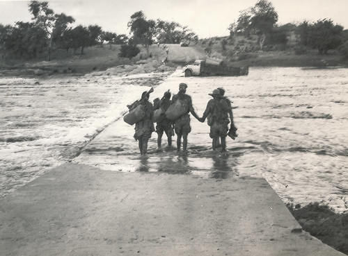 Moz government forces crossing a flooded bridge in Moz somewhere (1971)