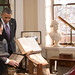 President Hollande examines Jefferson's revolving bookstand while President Obama looks on