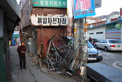 "Seoul Korea Hongje-dong backalley with rusty distressed sign and junk alongside newer parked cars - ""Old vs. New"" (moreska) Tags: travel tourism car contrast asia mess backalley rusty korea oldschool wear faded seoul handpainted signage pedestrians juxtaposition narrow crusty cracked clutter decayed piles rok oldvsnew hangul handcarts hongjedong"