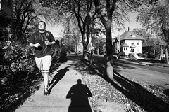 Hipstake (local paparazzi (isthmusportrait.com)) Tags: street autumn trees homes windows light shadow portrait blackandwhite bw music white house selfportrait motion black fall texture me contrast canon dark eos is pod downtown shadows zoom action candid details wide citylife fake highcontrast running run mp3 foliage sidewalk bark porch headphones mistake usm af madisonwi hip capture jogging ran jog ef fromthehip runningaway earbuds simplelife autofocus stride notlooking isthmus f4l 24105mm 2013 comingatyou danecountywisconsin photoshopelements7 canon5dmarkii pse7 localpaparazzi redskyrocketman lopaps hipstamatic hipstake