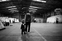 father and son (dominic_wenger) Tags: greece sindos thessaloniki athen frakapor refugee refugees refugeecamp camp military crysis borders open world problem swisscross volunter help portrait face family poor man woman kids chil child children beautiful beauty war syria tent tents hall light dark cold candid looking people human humanity sun boring life flee volunteer frame sigma35 sigma canon 5dmk3 lowlight sigmaart black blackandwhite blackwhite bw mono monochrome contrast humanism father son young boy holding hands holdinghand cute sweet happy walk stand