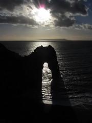 Through Durdle Door (shaggy359) Tags: door sea sky cloud sun sunlight english water silhouette clouds portland bay waves arch halo wave dorset through burst weymouth channel durdle