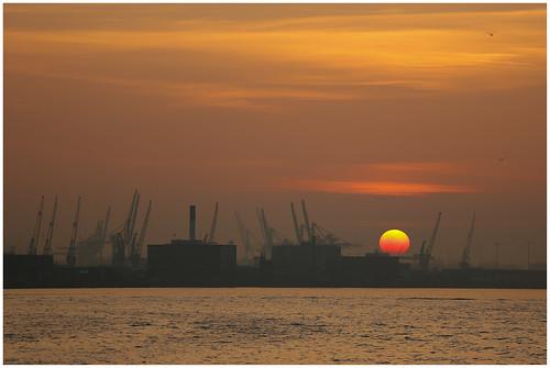 Zonsondergang over de haven in Rotterdam vanaf Hotel New York ...
