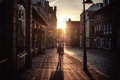 into the sun (ewitsoe) Tags: street city morning winter light people woman man sunshine architecture sunrise 35mm dawn lights march early streetlight cityscape crossing earlymorning poland sunny cobblestones oldtown earlyspring poznan jezyce nikond80 ewitsoe erikwitsoe
