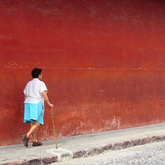 quotidien (Kalense Kid) Tags: street red woman crimson cane wall maroon candid guatemala sidewalk antigua walkingstick cobbles
