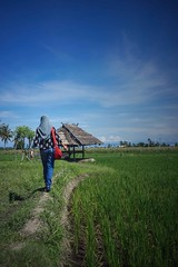 Walking through paddy field (Syahrel Azha Hashim) Tags: horizon lombok walking sony clearsky indonesia holiday simple paddyfields details dramaticsky tropicalisland 35mm rice hijab a7ii ilce7m2 sonya7 dof prime hut touristattraction headgear detail getaway shallow tropicalclimate handheld people colorimage vacation destination handbag light bluesky naturallight summer colorful lombokisland beautiful travel syahrel woman slingbag colors green oneperson agriculture 2017 field
