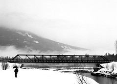 Lonely By the Bridge (dubbledott) Tags: revelstoke bridge lonely alone umbrella rain snow person people pentax 645 120 film analog hp5 ilford trees mountain river cold wet