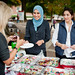 Wajeha Barakat (center) and Lina Shahin (right) offer a cupcake to judge Dr. Anita Flick.