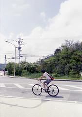 知念 自転車に乗るひと Nanjo-si, Okinawa (ymtrx79g ( Activity stop)) Tags: color slr film bicycle japan analog nikon kodak 35mmfilm okinawa 135 沖縄 kodakgold100 自転車 街 写真 銀塩 フィルム 南城市 nikonaisnikkor28mmf28 歩行走行 walkandrun 201310blog nanjosi streetnikonnewfm2